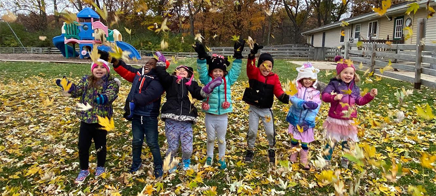 saline schoolchildren playing in outdoor area in fall leaves