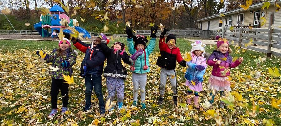 saline schoolchildren playing in outdoor area in fall leaves