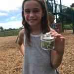 child holding caterpillar jar outdoors