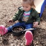 toddler in outdoor learning environment with wood chips