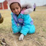 child outdoors making leprechaun traps in dirt
