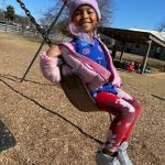child playing outdoors in swing set