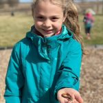 school age child playing with worms in outdoor learning environment