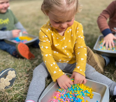 preschool toddler playing with beads in outdoor learning environment