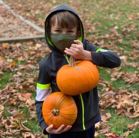 school age child wearing mask showing pumpkins outside