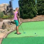 child playing putt putt on field trip